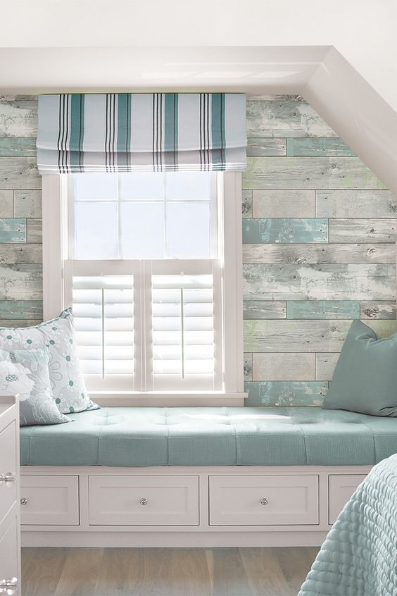 Coastal window bench with a blue cushion in a whitewashed wood wall