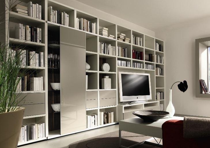 Modern white built-in bookshelves surrounding a TV