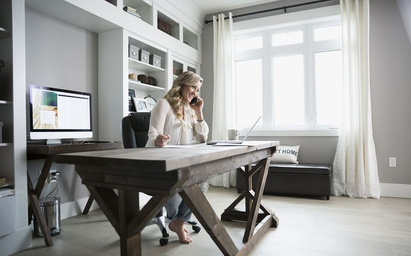 Young, millennial blond woman in neutral, contemporary rustic home office with rustic, wood, trestle desk