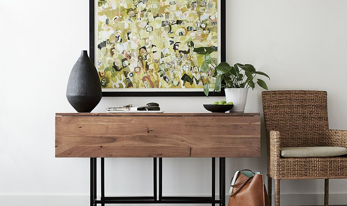 An example of modern console table styling with a walnut console table styled with a large modern abstract art piece over it, and a vase and plant set on top of it.